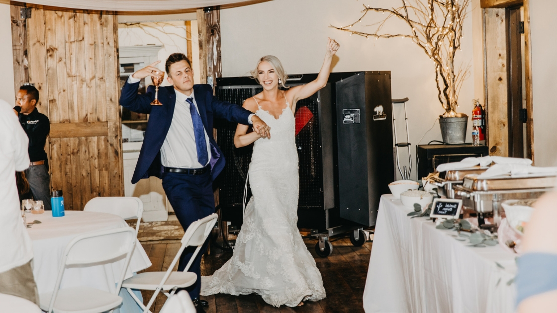 Bride and groom enter reception after wedding buffet smile happy