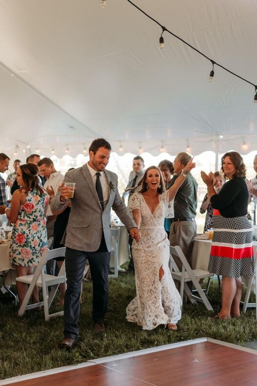 Bride and groom entering wedding reception in outdoor wedding under white tent at summer vineyard wedding
