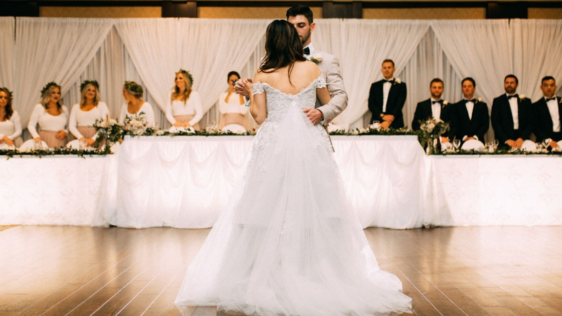 Bride and groom first dance hug and sway in center of dance floor bridal party stand at head table watching and smiling