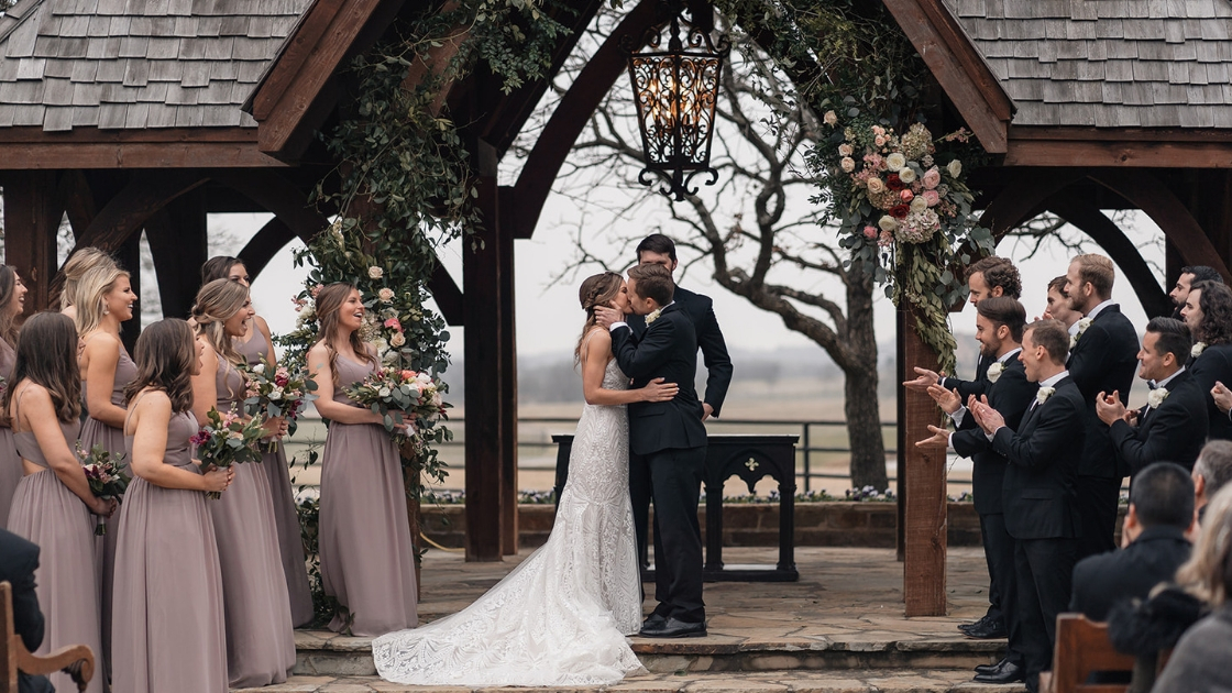 Bride and groom first kiss in revelry bridal gown bridesmaids in pink taupe chiffon dresses