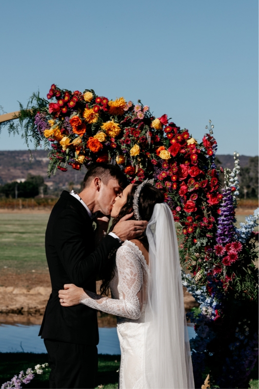 BRide and groom first kiss outdoor wedding ceremony red pink yellow florals with purple blue lace wedding dress