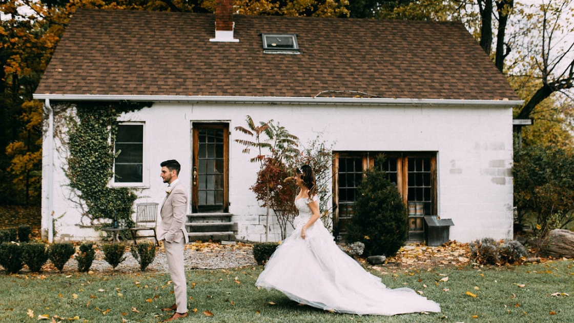 Bride and groom first look in front of gorgeous old houe with greenery foilage groom in grey suit waiting for bride