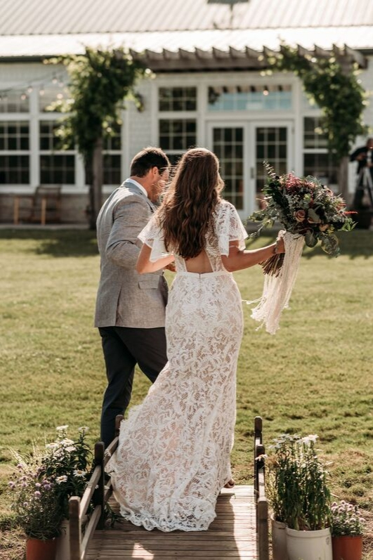Bride and groom holding hands and walking away after wedding ceremony as husband and wife back shot lace bridal gown wedding dress florals