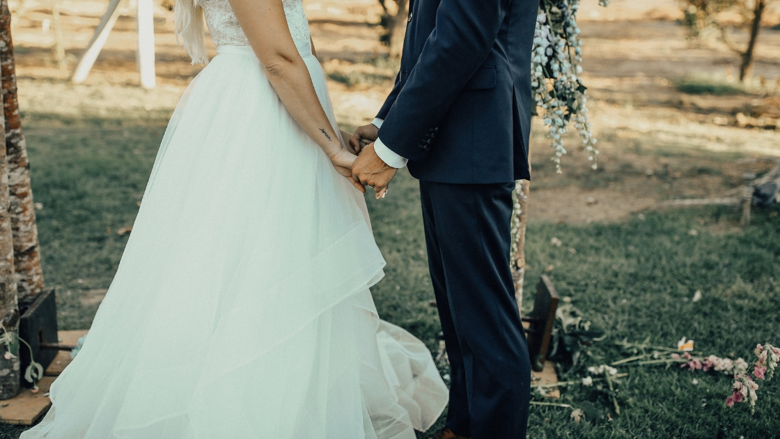 Bride and grooms hands on their wedding day in desert california ceremony