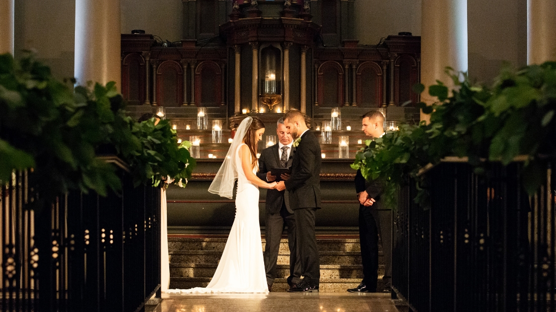 bride and groom holding hands with candles inn the background on wedding day best man looking at his friends get married in gorgeous hall