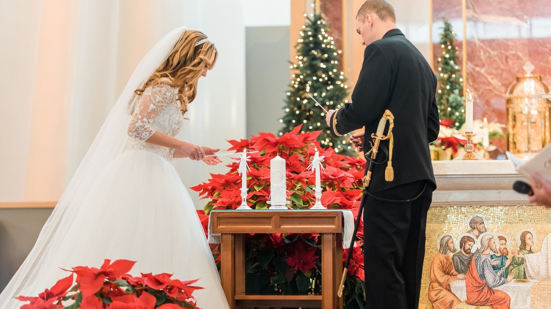 bride and groom in princess outfit light holiday wedding christmas candles with red flowers and christmas trees in venue