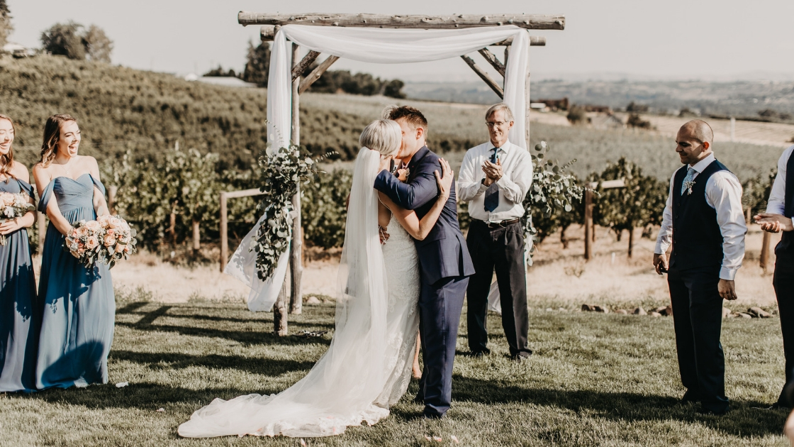 Bride and groom kiss at alter wedding day vinyard beautiful love relationship