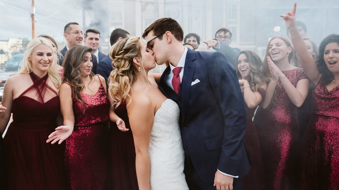 bride and groom kissing with bridesmaids cheering and laughing in the back love burgundy dress sequins and tulle revelry