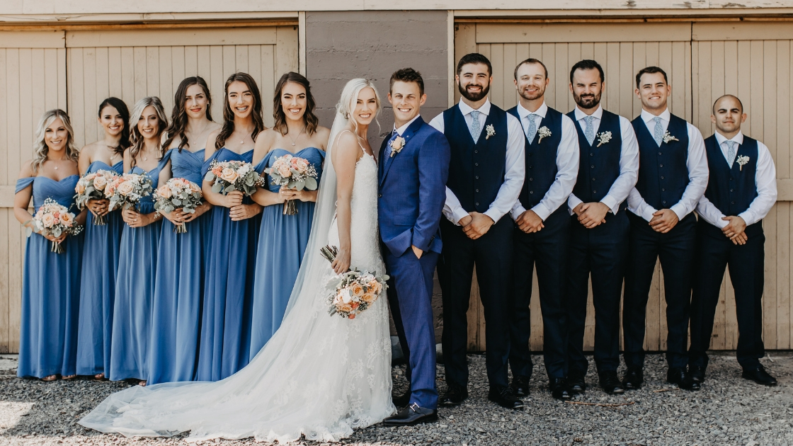 Bride and groom smile and post on wedding day with bridesmaids and groomsmen in blue