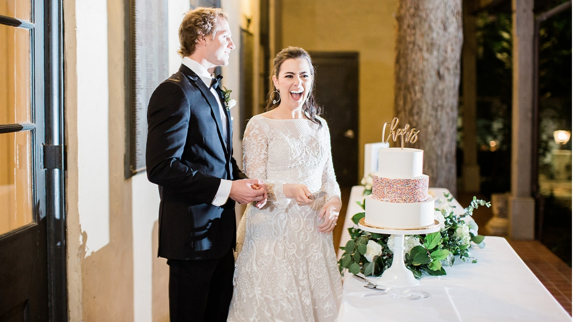 Bride and groom standing by three tier white and sprinkle wedding cake with cheers writter at the top cutting cake on wedding day