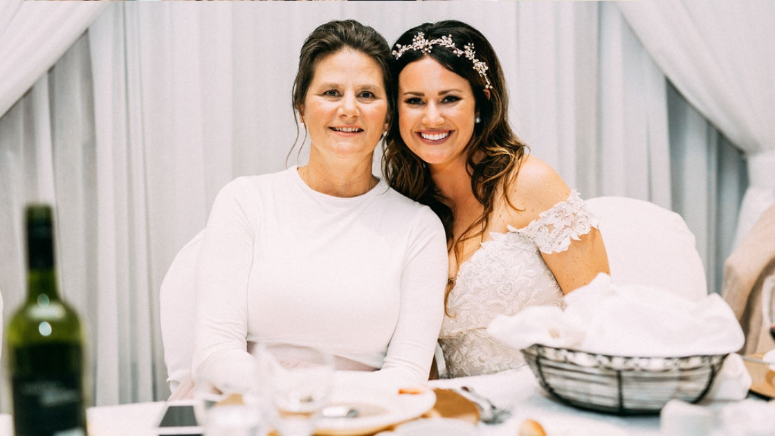 Bride and mom who was a bridesmaid smile and pose on wedding day at head table celebrating fall october wedding