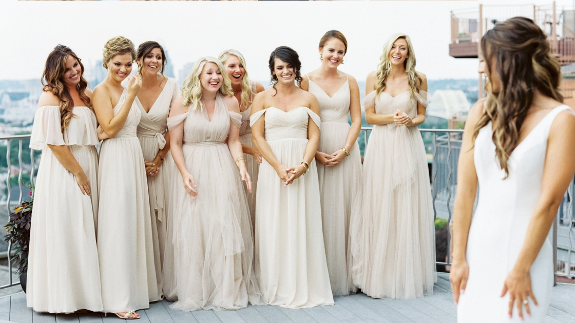 Bride first look with eight bridesmaids on porch on wedding day in tulle and chiffon revelry bridal gowns neitrals