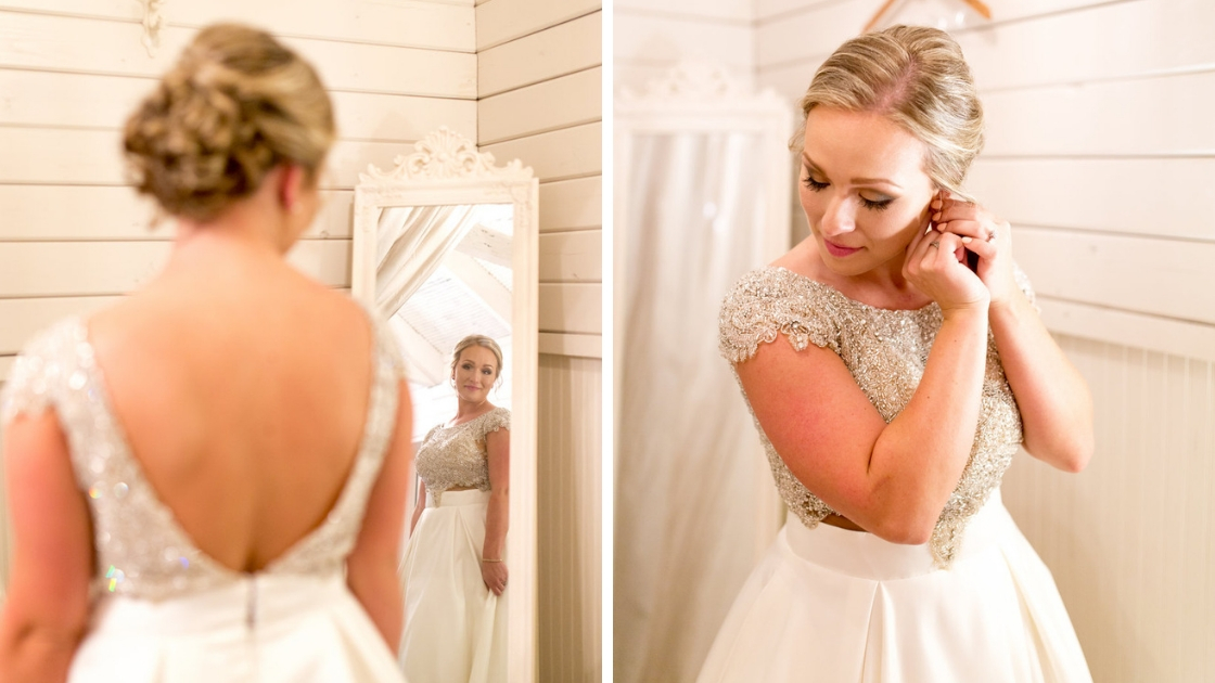 Bride gets ready on her wedding day looks in mirror and puts earrings in