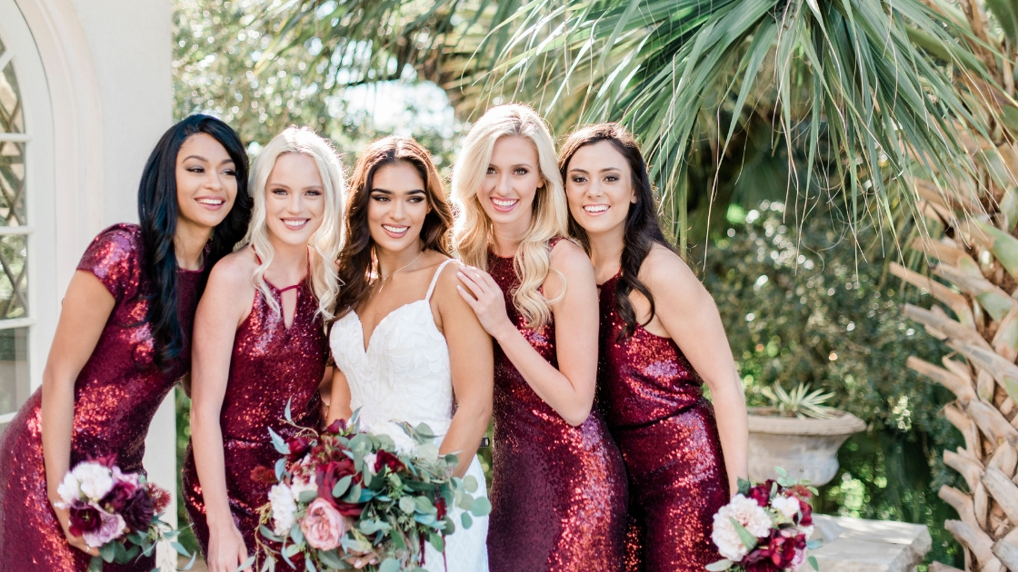 Bride in art deco sequin revelry wedding dress white poses with four bridesmaids in revelry cabernet sequin styles separates mix and match