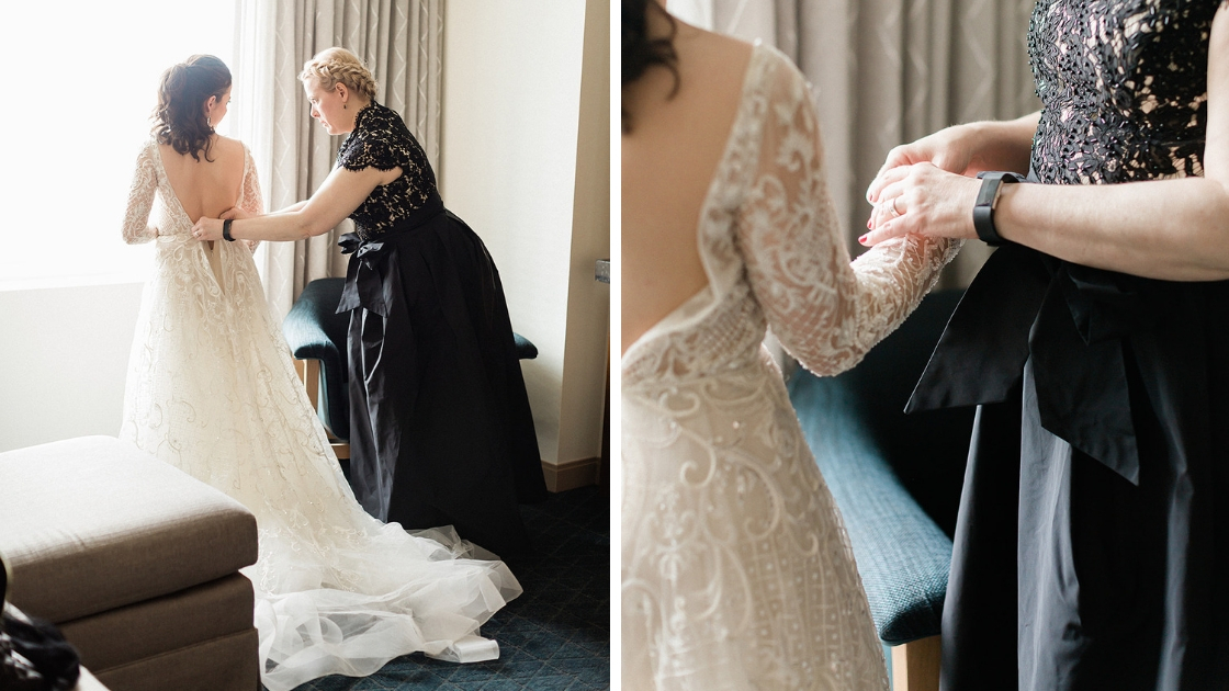 Bride in beautiful art deco lace wedding dress gets zipped up by mom in black dress on wedding day detail shot of mom helping at wedding