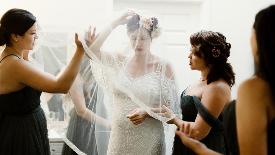 Bride in boho dress puts on veil over face with floral crown bridesmaids help her get ready to walk down aisle