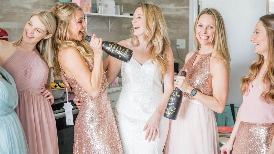 Bride in decklyn lace bridal gown bridesmaids in rose gold bridesmaid gowns and separates blush chiffon dresses black champagne bottles gold lettering