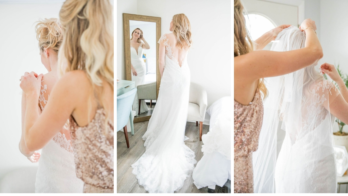 Bride in lace v neck bridal wedding dress maid of honor helping put on dress rose gold hazel dress veil help deep dress wedding dress bridal gown revelry pose in front of mirror