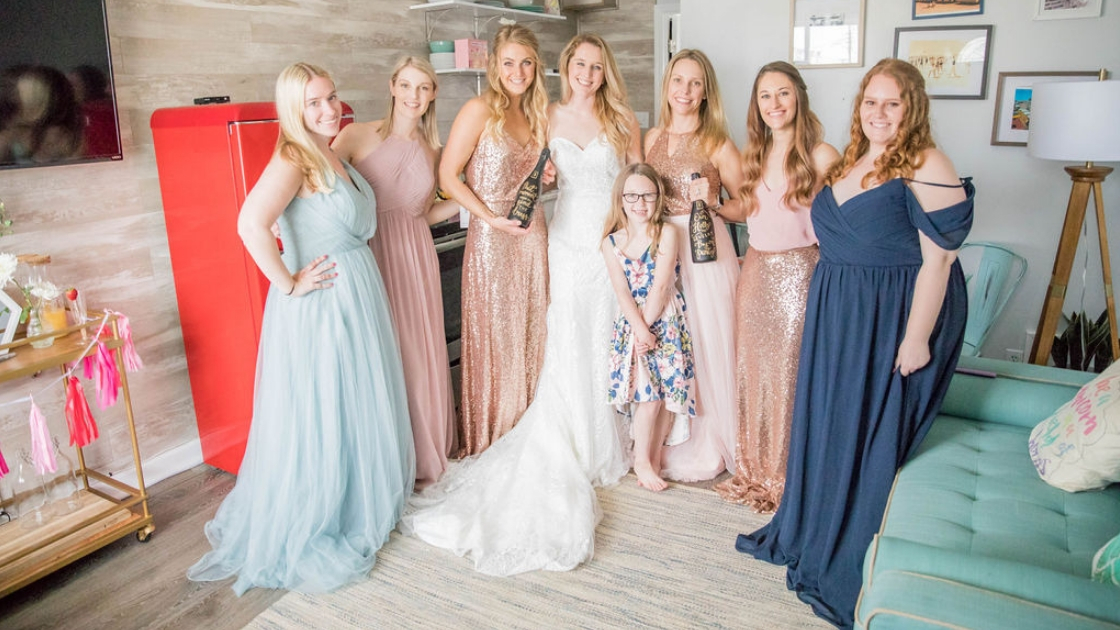 Bride in Revelry decklyn bridal gown at revelry try on party in nyc with bridesmaids in chiffon tulle and sequin dresses blue blush pink rose gold chanpagne black bottles gold lettering