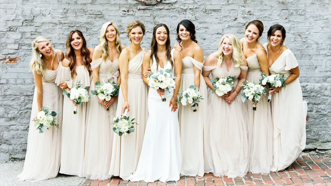 Bride in sleek white bridal gown eight bridesmaids in champagne neutral gowns tulle and chiffon holding white roses greenery white brick wall
