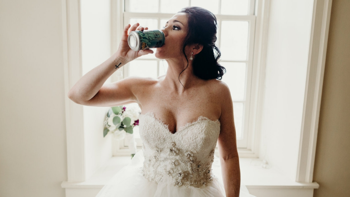 Bride in strapless lace bedazzled floral wedding dress drinking beer on wedding day before walking down the aisle