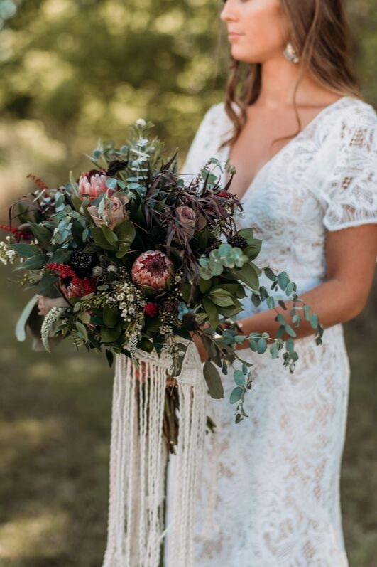 Bride in vintage lace offwhite wedding dress holds bouquet of greenery, roses, pink and green florals boho bridal gown bride look