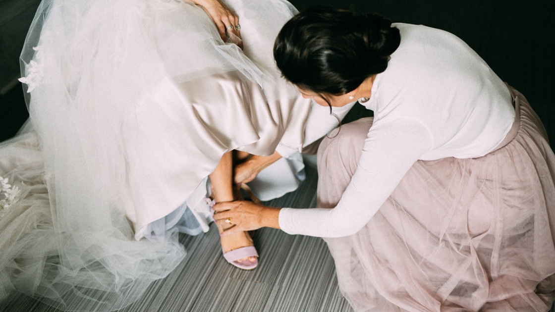 Bride in wedding dress getting ready before ceremony tulle dress mother helping put on pink shoe in pink skylar skirt
