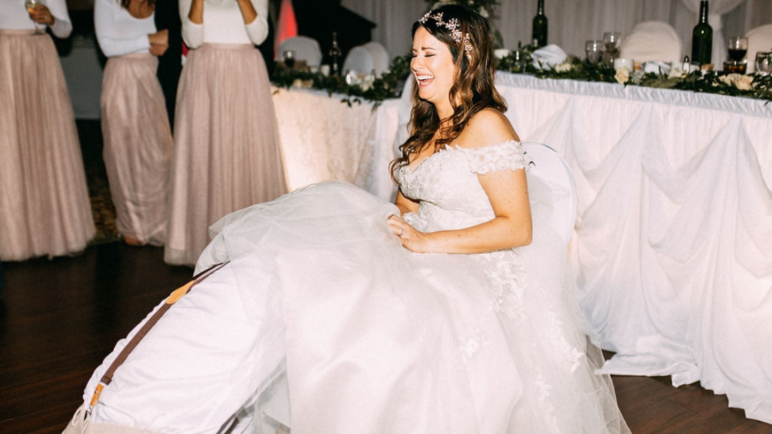 Bride laughing sitting groom under dress for garter laughter bridesmaids in pink tulle dresses in front of banquet table
