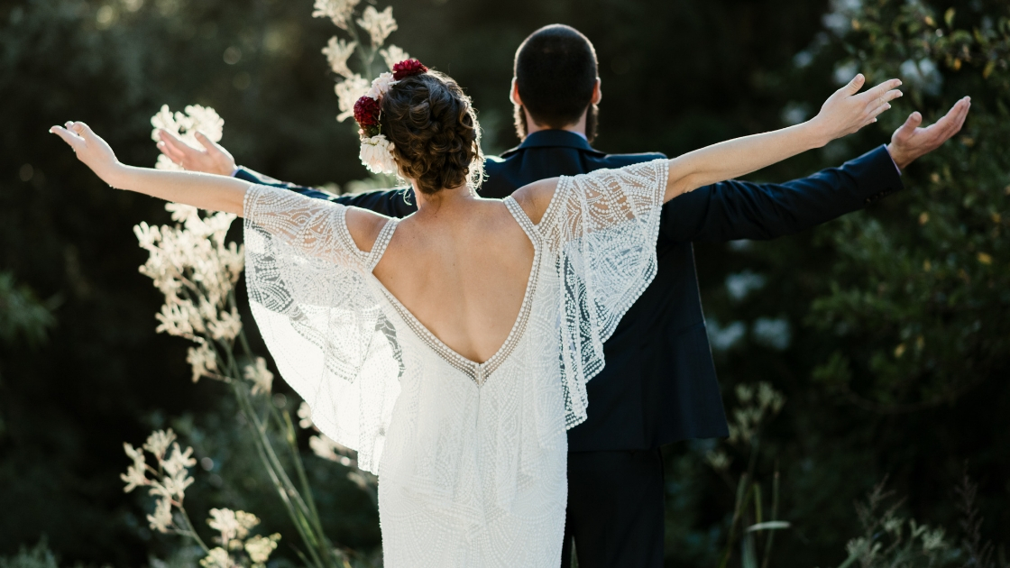 Bride off the shoulder dress with wings and groom put arms out and face away as they celebrate on their wedding day forest redwood