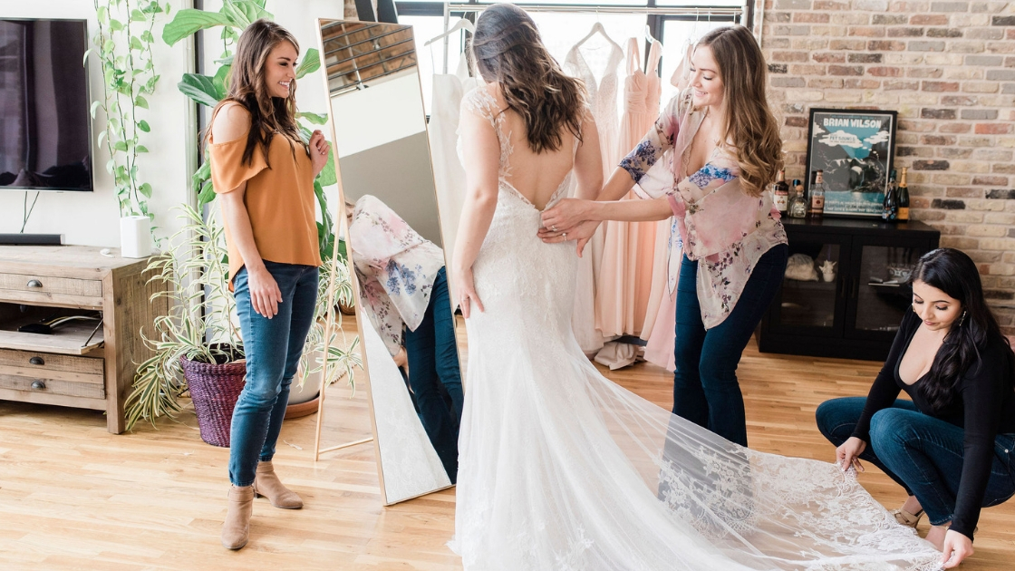 Bride posing in mirror with beautiful revelry bridal gown with lace train as three bridesmaids zip up and smooth train at revelry try on party in austin texas