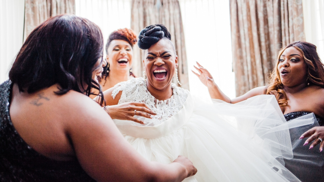 Bride putting on wedding dress on wedding day laughing with bridesmaids in black sequin dresses tulle wedding dress