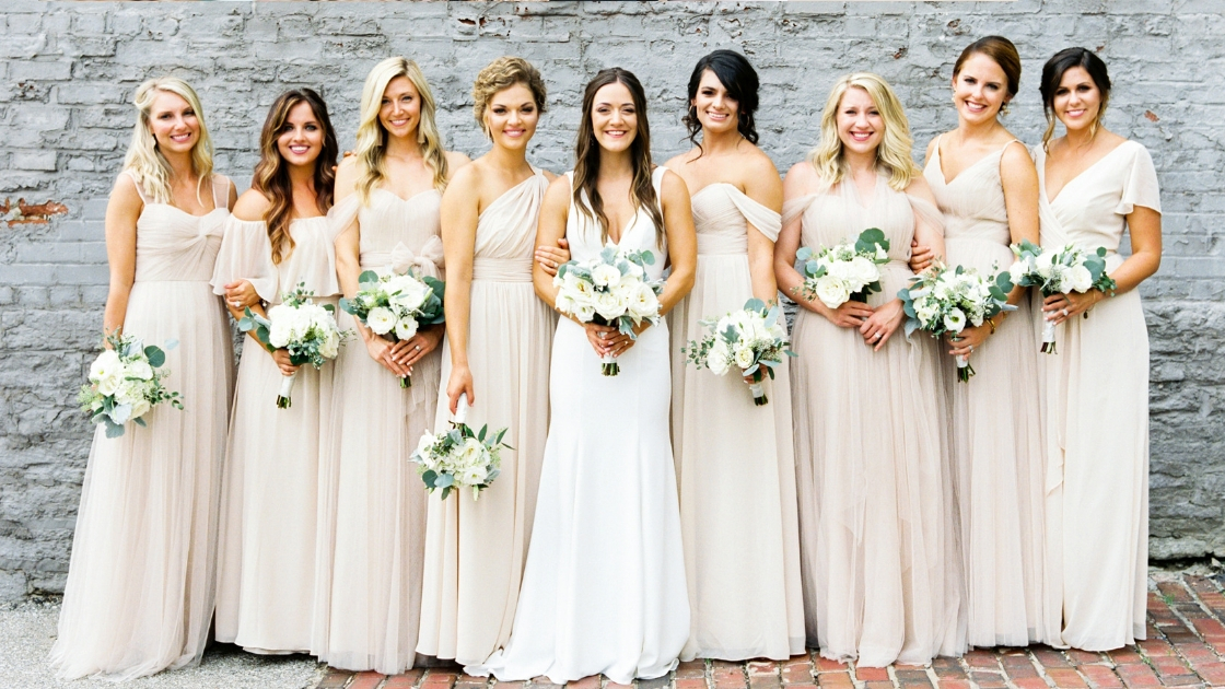 Bride standing with eight bridesmaids tulle chiffon champagne revelry bridal gowns neutral gowns white and green florals