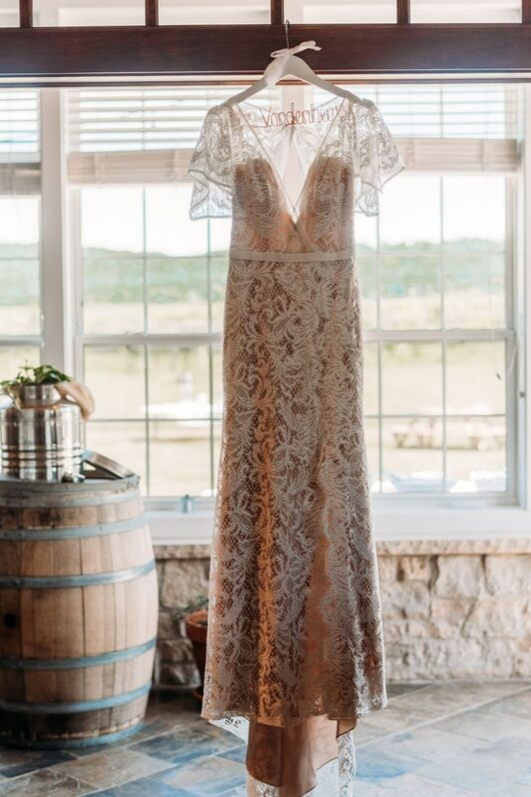 Bride wedding day lace dress off white vintage gown hanging up shot pretty window vineyard june wedding