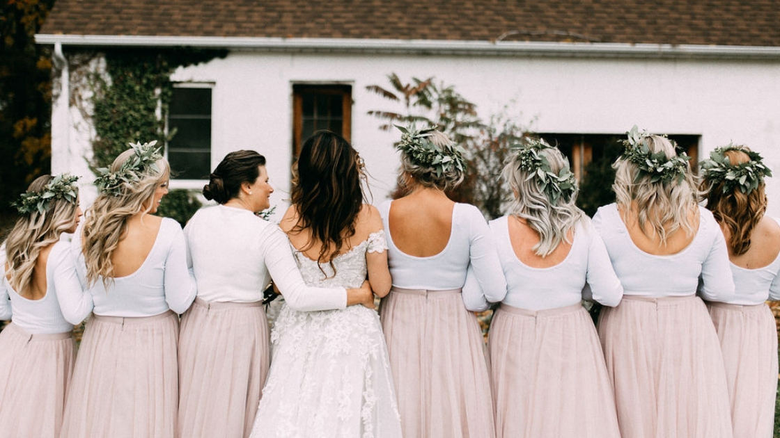 Bride with 7 bridesmaids and mother in pink tulle skirts facing back greenery flower crowns long sleeve white shirts