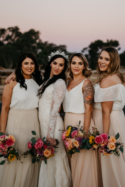 Bride with three bridesmaids smiling and posing in blush and white outfits on wedding day with bright florals and sun setting in background