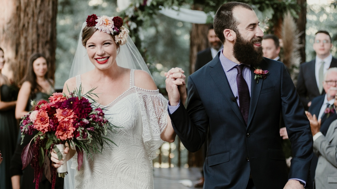 brides and groom walk back down aisle after wedding all smiles holding bouquet and boutioneer flower crown pink and orange forest