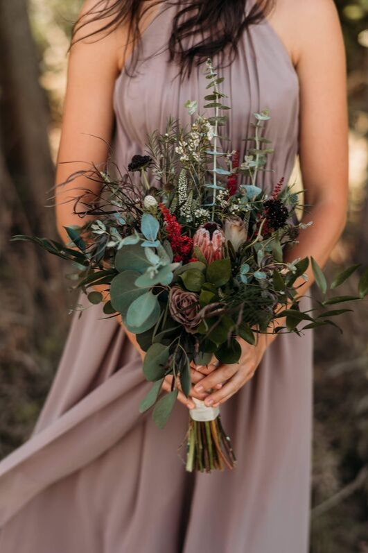 Bridesmaid detail photo melted mauve wrap chiffon dress eliza gown greenery floral bouquet pink and red florals