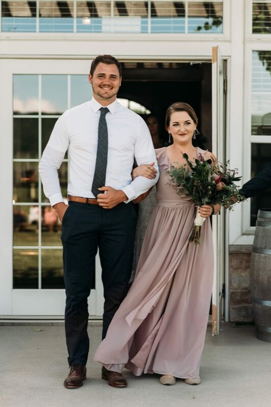 Bridesmaid in Valerie chiffon dress in melted mauve bridesmaid revelry dress walking down asile on wedding day