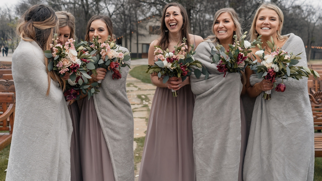 bridesmaid on cold wedding day outside in pink taupe mauve chiffon dresses flowers wrapped up outside after ceremony