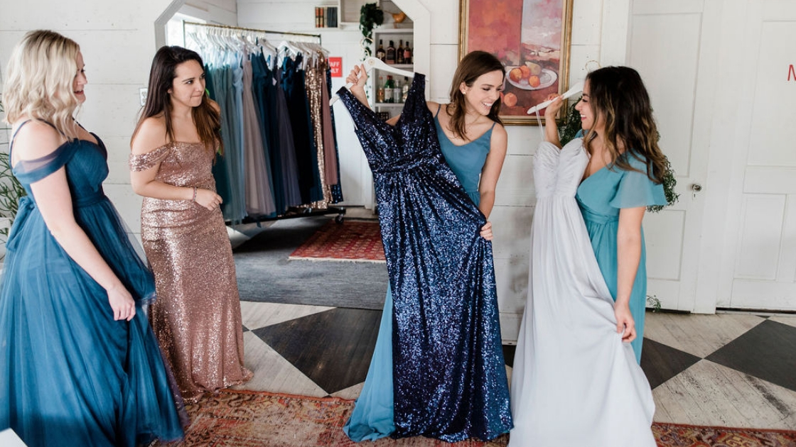 Bridesmaids in blue hold up dresses in chiffon and sequin navy and light blue to decide what they want to wear at Revelry try-in party wedding