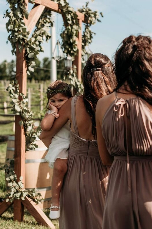 Bridesmaids in chiffon revelry dresses melted mauve taupe dresses standing at alter on wedding day flower girl tired being held in white dress