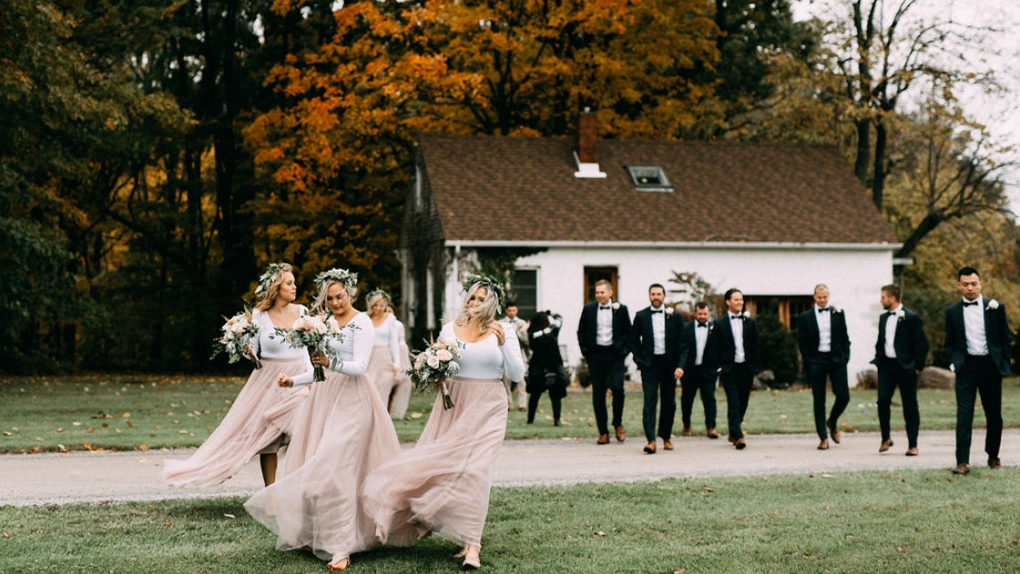 Bridesmaids in pink tulle skirts and flower crowns walk in wind at wedding venue with groomsmen in back walking to wedding on beautiful fall day