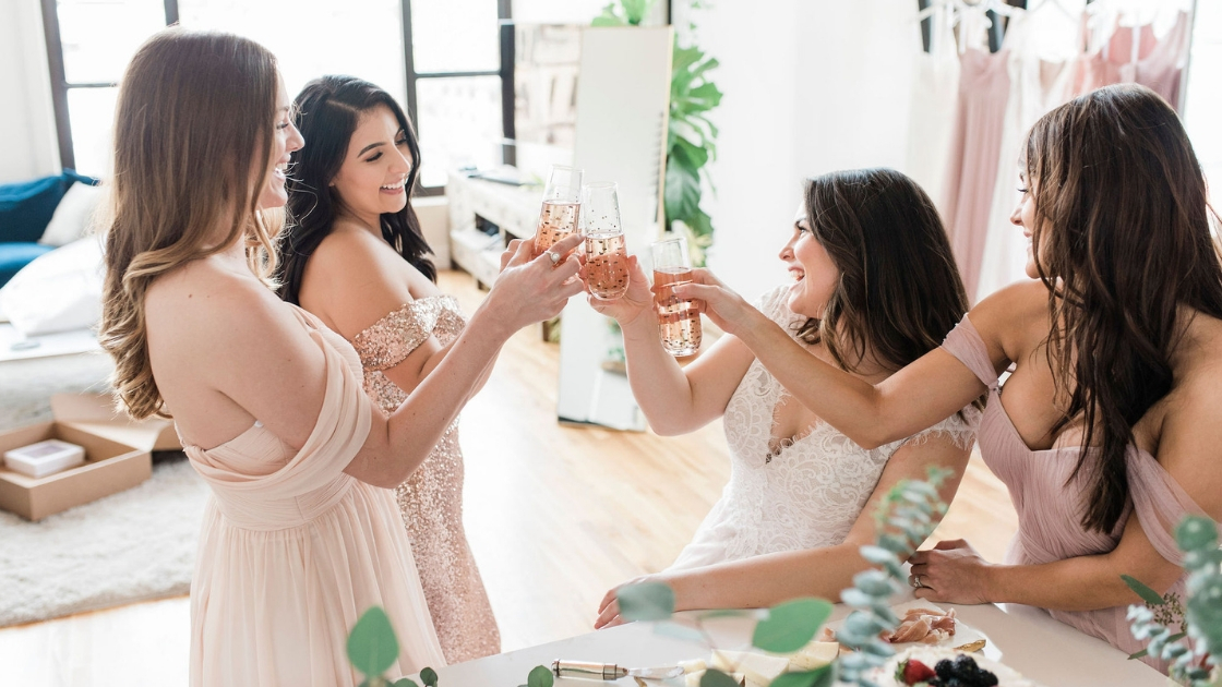 Bridesmaids in revelry bridesmaid pink and blush and rose gold sequin dresses and bride in ravina wedding dress bridal dress cheersin beautiful lighting at downtown austin loft with greenery and snacks all around