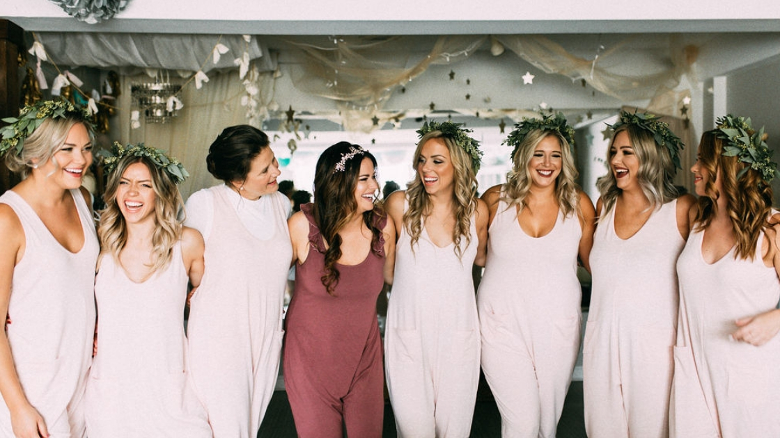 Bridesmaids in rompers smiling and posing with greenery headbands pockets getting ready on wedding day