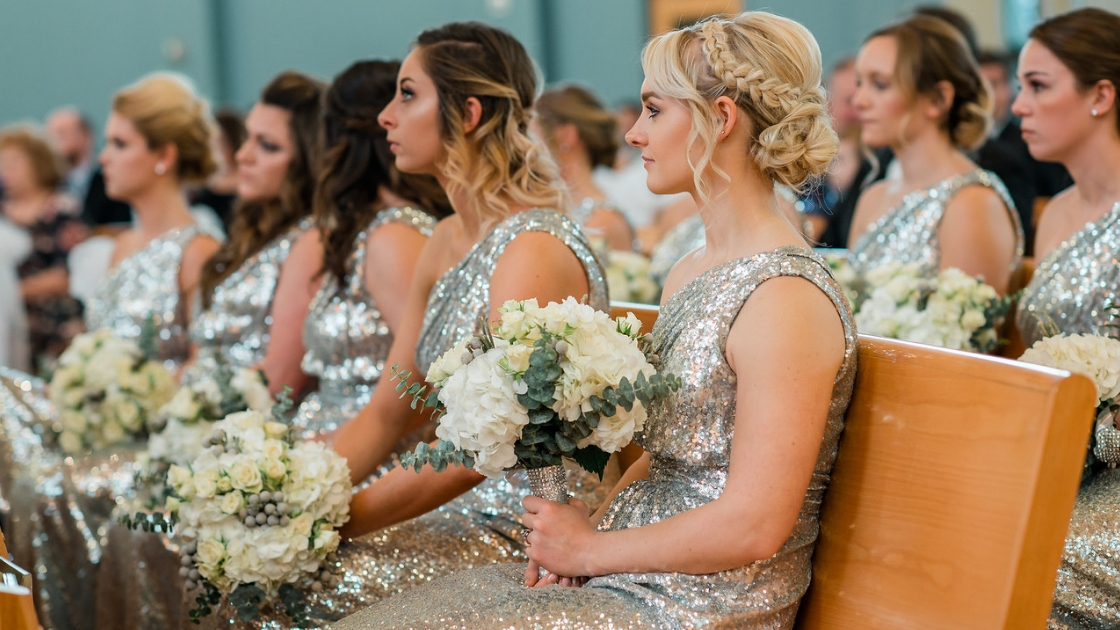 bridesmaids in silver sequin dress hold white holiday bouquts looking festive and sparkling