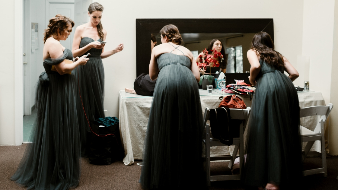 Bridesmaids in tulle eucalyptus green blue rosalie revelry dresses primp and look at phones before friends wedding