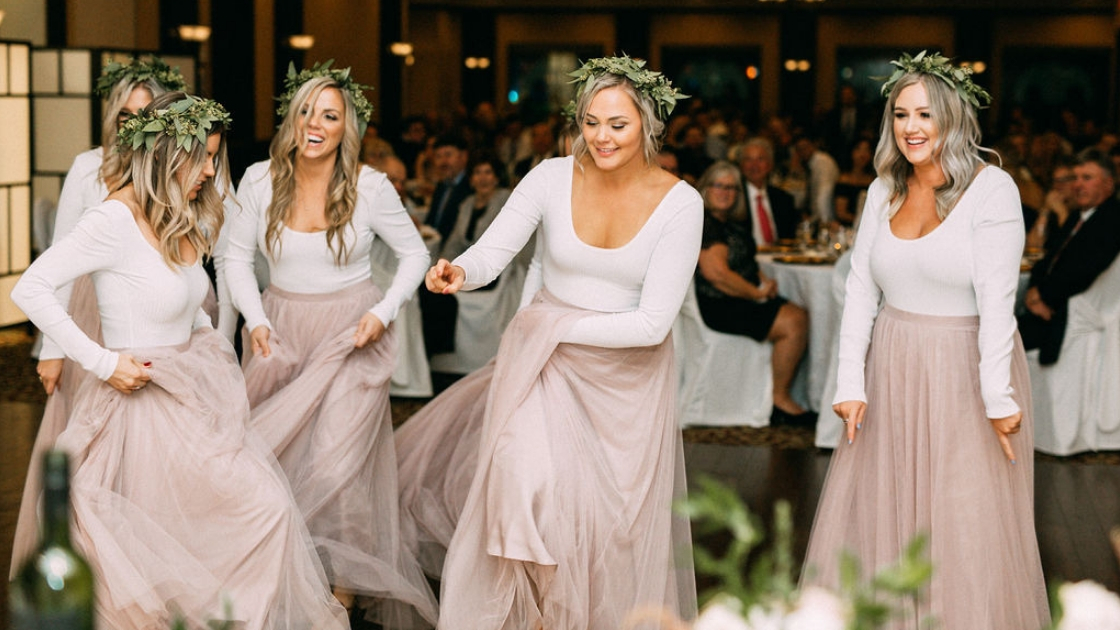 Bridesmaids in tulle pink bridesmaid dresses with long sleeve white shirts put on dance performance at wedding day laughing love reception