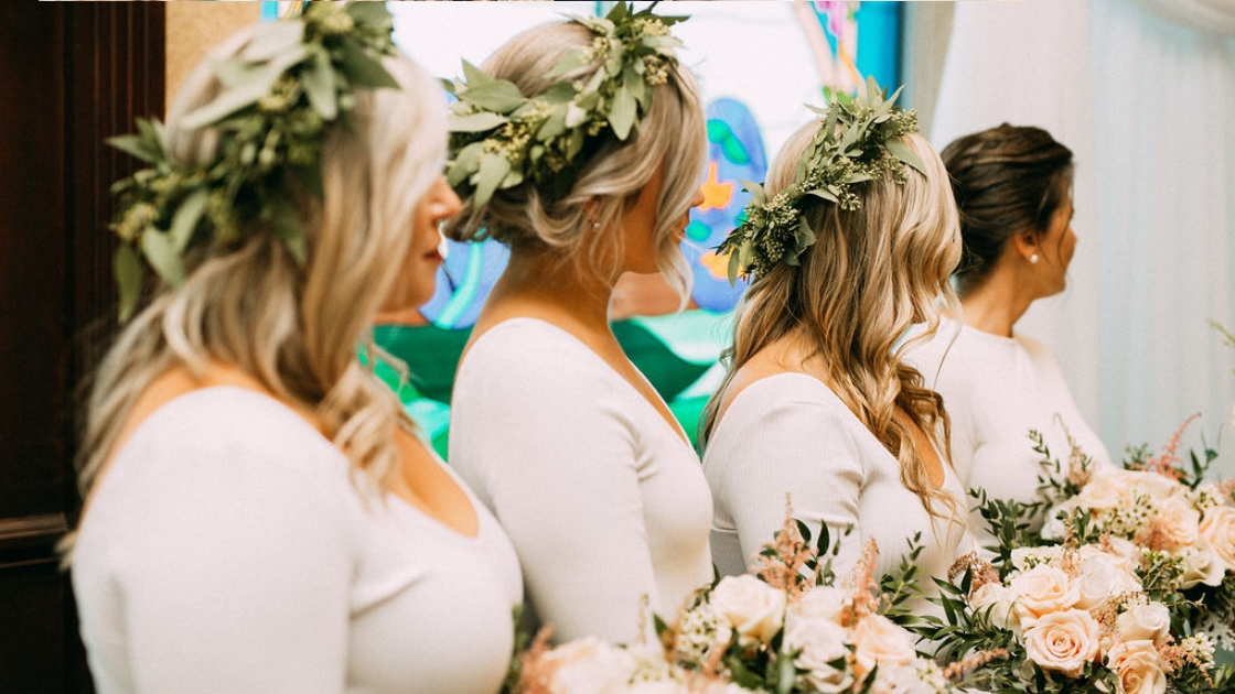 Bridesmaids in white long sleeve shirts holding pink and green flowers and greenery crowns smile and watch as best friend walks down the aisle