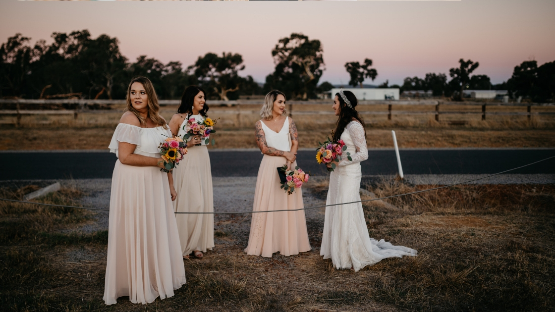 bridesmaids posing and waiting to walk down aisle blush pink white chiffon colors holding bright bouquets on wedding day
