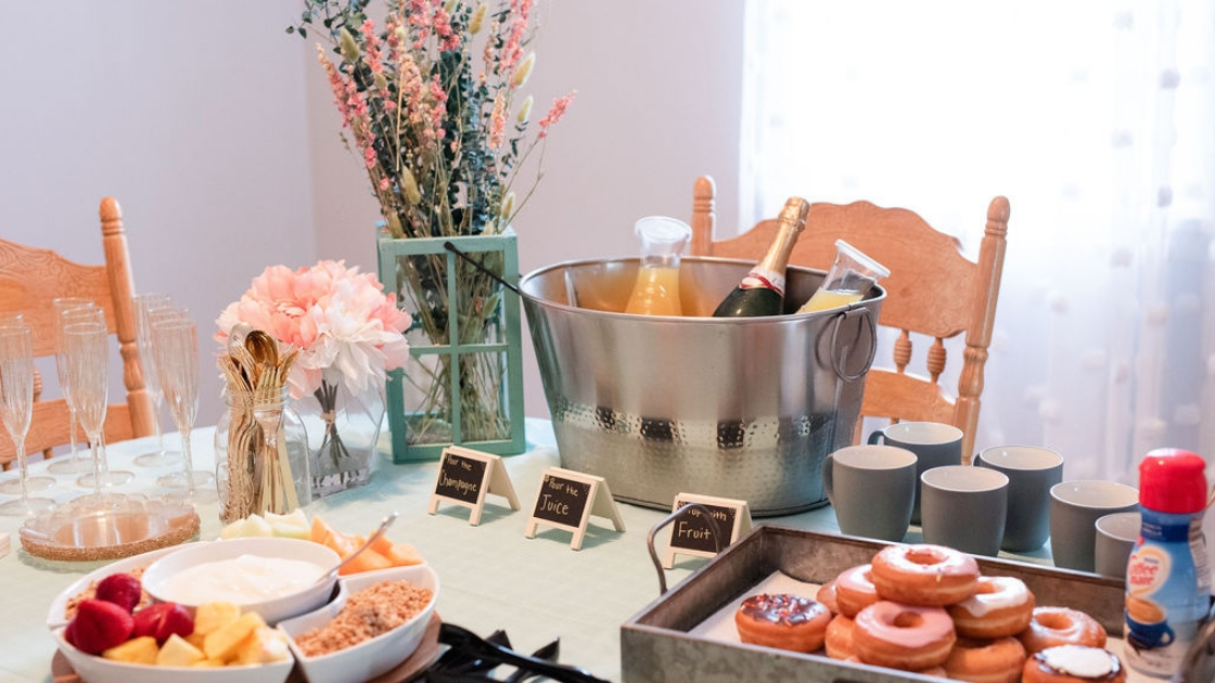 Brunch breakfast spread doughnuts mimosas pink and blue flowers and fruit flutes try-on party spread